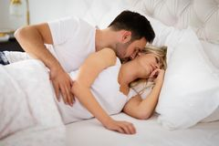 Passionate couple foreplay in bed. Passionate beautiful couple foreplay in bed royalty free stock photos