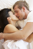 Passionate Couple Kissing In Bed stock photo
