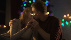 Passionate couple kissing near Christmas decorations with Bengal light in hands