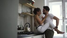 Couple in the kitchen, the girl sits on the table and the guy gently hugs her and they kiss Spbd