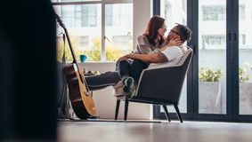 Passionate couple together at home. Passionate couple relaxing on armchair in living room. Woman sitting on lap of her boyfriend and looking at each other Royalty Free Stock Image