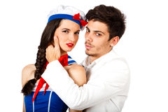 Passionate couple wearing sailor uniform. Passionate couple with young elegant men seducing sailor woman. Isolated on white background. High resolution studio Stock Photo