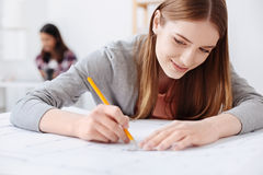 Passionate creative woman focused on the plan. Making thoughts real. Persistent talented pretty lady making a draft drawing on the new building while using some Royalty Free Stock Photos