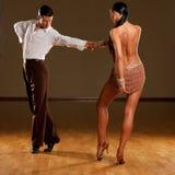 Passionate dancers dancing rumba. Passionate dancers in brown dress dancing rumba Royalty Free Stock Photos