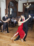 Passionate Dancers Performing Tango While Couple Dating In Resta. Full length of passionate dancers performing tango while couple dating in restaurant stock images