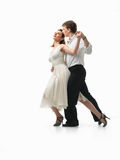 Passionate dancing couple on white background. Passionate, young couple showing interesting dance moves on white background Stock Images