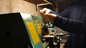 Passionate DIY man, he uses the lathe for DIY, in his home laboratory, precision work with metal lathe stock photos