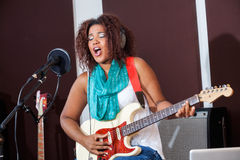 Passionate Female Singer Playing Guitar Royalty Free Stock Photos