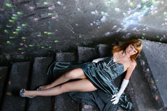 The girl in an evening dress lies on an old ladder Royalty Free Stock Image