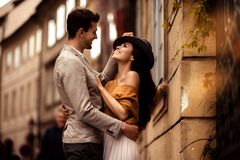 Passionate gorgeous young couple embrace each other while walk across ancient city. Cheerful elegant cute female model. Wears stylish hat, looks with cheerful Royalty Free Stock Photography