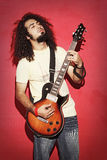 Passionate guitarist with beautiful long curly hair playing guit Stock Images