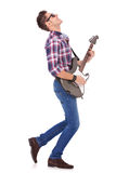 Passionate guitarist playing. Side view of a passionate guitarist playing his electric guitar on white background Royalty Free Stock Photo