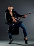 Passionate guitarist playing his electric guitar. On black Stock Photography
