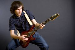 Passionate guitarist playing his electric guitar Stock Photos