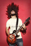 Passionate guitarist screaming with beautiful long curly hair pl Royalty Free Stock Photos