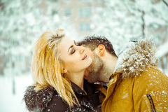 Passionate guy kisses girl with white hair in neck on street in Stock Photos