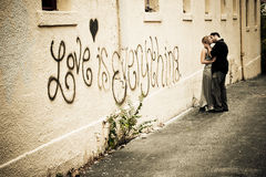 Passionate Kiss in the Alley. A young male and female expresses their passion for each other by kissing in an alley. Love is everything is written on the wall stock photo
