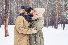 Passionate kiss of young married couple under the snowfall Royalty Free Stock Images