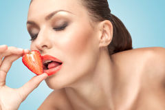 Passionate lady. A beautiful girl licking a red juicy strawberry with a temptating tongue Stock Images