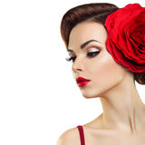 Passionate lady with a red flower in her hair. Beautiful lady with a big red flower royalty free stock image