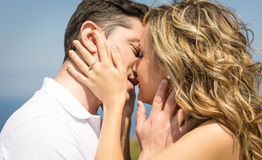 Passionate love couple kissing on a summer day. Passionate beautiful love couple kissing outdoors in a summer day over nature background royalty free stock image