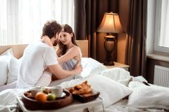 Passionate male and female embrace each other, look with love, spend their honeymoon in luxury hotel, enjoy delicious stock photo