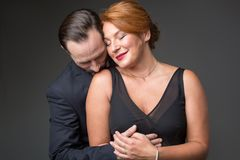 Passionate married couple embracing with love. Waist up portrait of glad middle-aged women enjoying hug of her husband. Man is standing and kissing female Royalty Free Stock Images