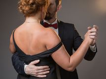 Sensual loving couple expressing their passion in dance. Passionate middle-aged men and women dancing. Focus on women back wearing black dress Stock Photography