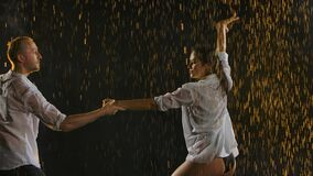 Passionate movements of a couple dancing salsa in the rain. A dance that brings bodies closer. Slow motion. Close up.
