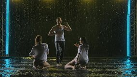 Passionate movements of a salsa dance in the rain on a dark smoky backlit background. A silhouette of three wet bodies