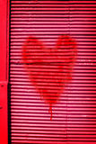Passionate red heart for a Valentine love. Passionate red heart for a Valentines sweetheart symbolic of love and desire spray painted on a vivid red metal wall Royalty Free Stock Photo