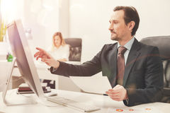 Passionate resourceful businessman comparing the data Stock Photo
