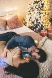 Couple on bed. Passionate romantic couple spending time before New Year near beautiful Christmas tree at home. Sexy young women and handsome men are lying on bed Stock Image