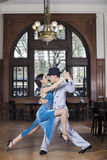 Passionate Tango Dancers Performing In Restaurant. Full length of passionate male and female tango dancers performing in restaurant Stock Images