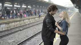 Passionate teen couple blowing kisses and hugging waiting in railway train station before trip stock video footage