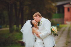 Passionate wedding kiss. Unforgettable wedding day. Happy and romantic bride and groom at the wedding walk Stock Image