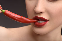 Passionate woman biting hot chili royalty free stock photos