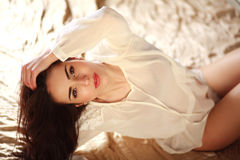 Passionate young brunette woman relaxing lying in lingerie Stock Photography