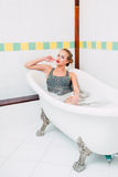 Passionate young caucasian blonde girl lying in white bathroom Royalty Free Stock Photography