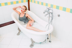 Passionate young caucasian blonde girl lying in white bathroom Stock Images