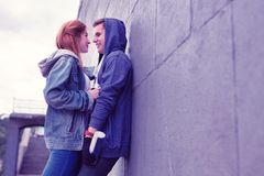 Passionate young couple having lovely moments while leaning on the wall royalty free stock image