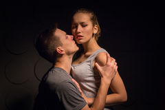 Passionate young couple in the room. And the darkness around stock images