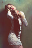 Passionate young woman. Young passionate woman in lace dress lean against the grunge wall royalty free stock photo