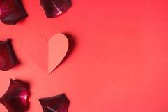 Passionbegrepp för valentin dag med mörker - röda roskronblad och en pappers- hjärta Royaltyfria Bilder