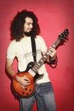 Passionerad gitarrist som är lycklig med härlig lång playin för lockigt hår royaltyfri foto