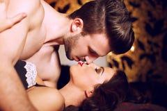 Passionerade par som kysser i säng Fotografering för Bildbyråer