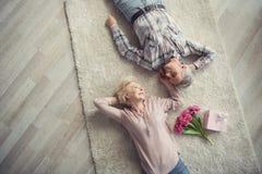 Passionerat mogna par som vilar på golvet fotografering för bildbyråer