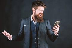 passionerat om arbete Sk?ggig man som ropar p? smartphonen direktanslutet och l?ttr?rligt Brutal caucasian hipster med mustaschen arkivfoton