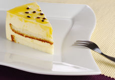Passionfruit Cake. A piece of passionfruit cake on white plate with cake fork (Selective Focus Royalty Free Stock Image