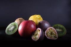Passionfruit, kiwi, lemon and peach on dark background, moonligh Stock Photos